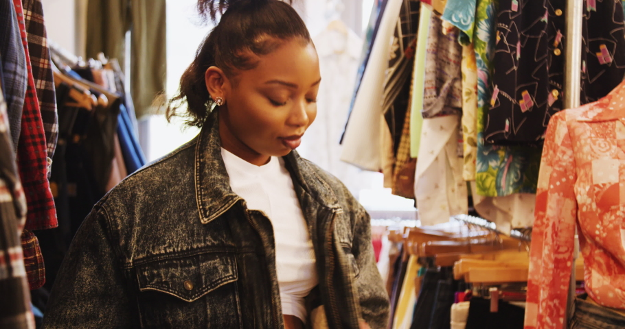 young black woman in a vintage clothes shop, trying on denim jacket with fake fur lining