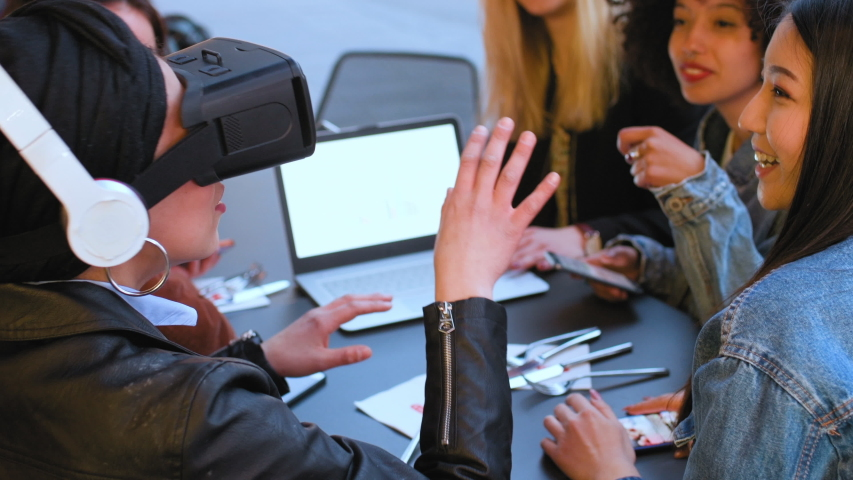 A girl among a group of friends wearing a Virtual Reality headset, moving her hands and her friends laughing and talking.