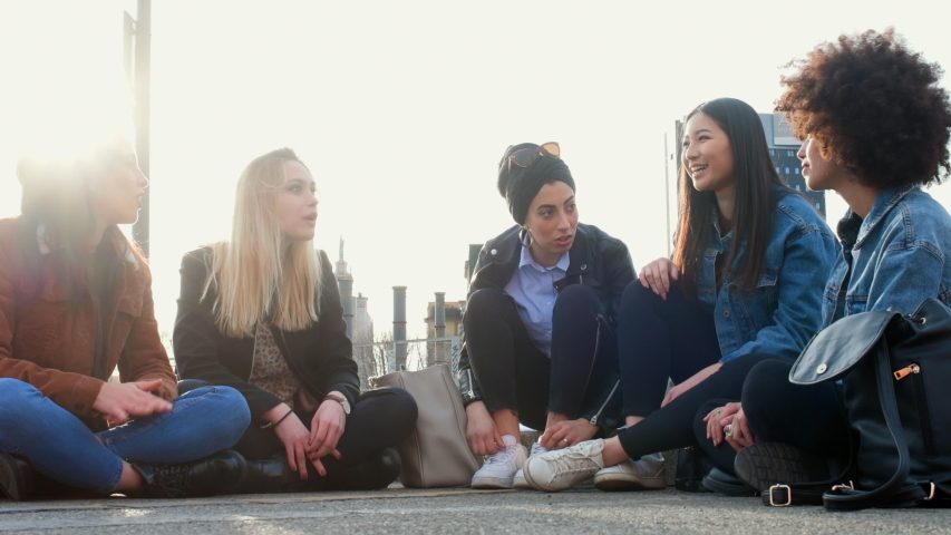 A group of girls, young women, female friends sitting on the ground talking and laughing.