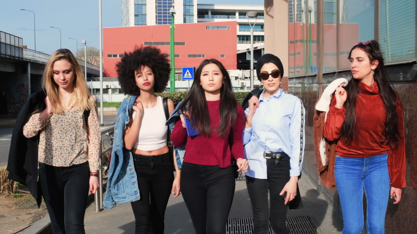 A group of girls, young women, female friends in a gang out on the streets of a city.
