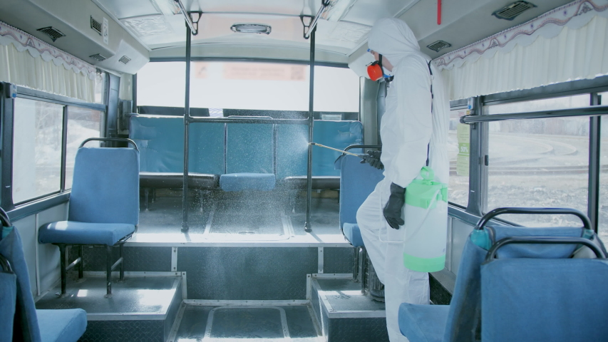 Man Disinfect Bus. Covid-19. Corona Virus Disinfection Transport. Antiseptic Sanitizer. Coronavirus Disinfectant. Worker Wear White Uniform Suit. Protect Mask covid 19. Spray Disinfecter corona virus. Royalty-Free Stock Footage #1054085963