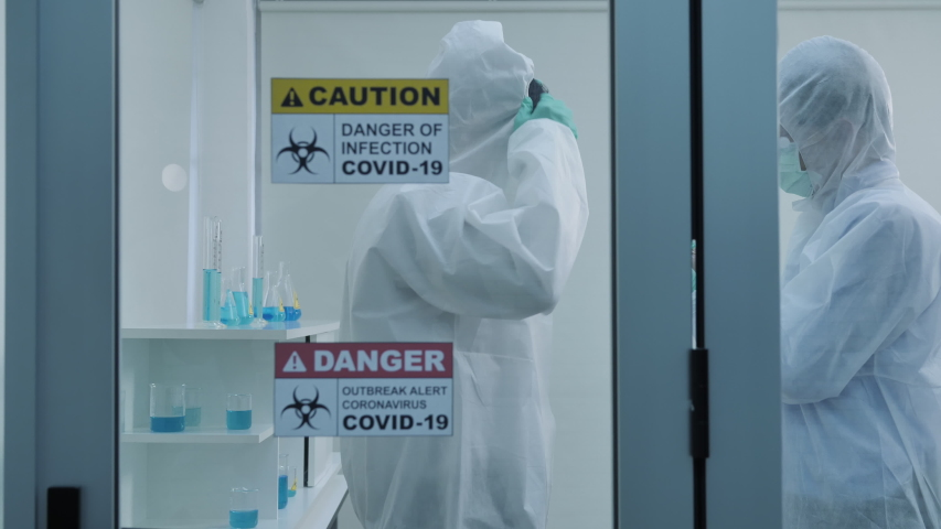 Two asian scientist is wearing Personal Protective Equipment (PPE) in laboratory. Protection coronavirus or covid19 and Medical experiment concept. Slow motion Dolly slider shot | Shutterstock HD Video #1054088831