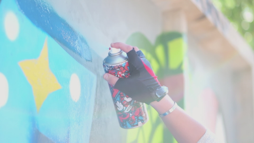 Beautiful Young Girl making a colorful graffiti with aerosol spray on urban street wall at summer. Creative art. Talented female hipster student drawing picture. Freedom, lifestyle, culture concept.
