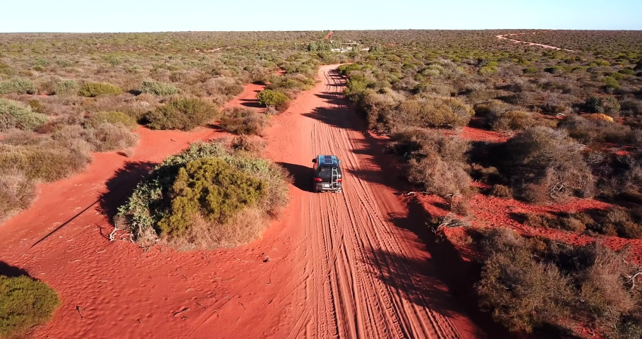 Van driving on red sand road travel drone camper Royalty-Free Stock Footage #1054092287