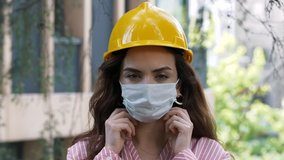 Portrait of female construction worker in medical mask and overalls on background of house under construction.4k slow motion video.