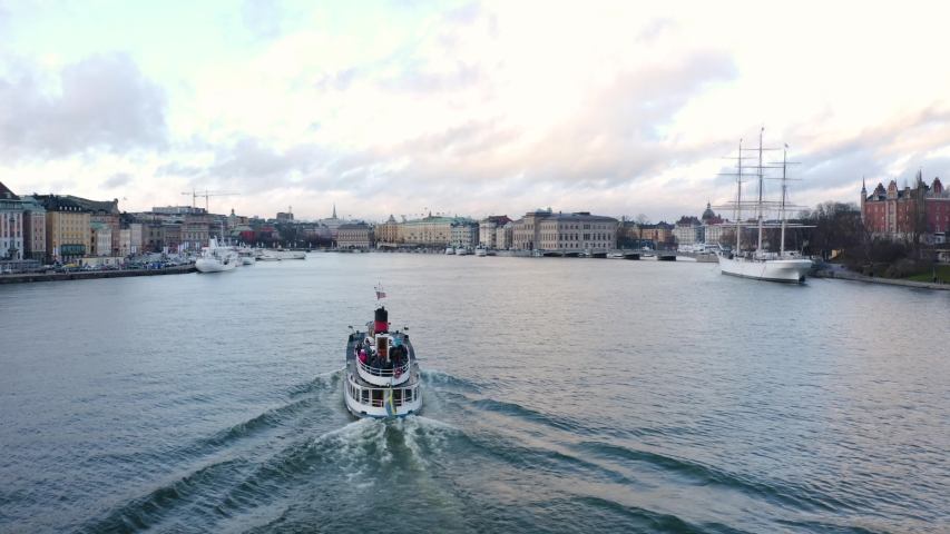 Aerial shot of tourist boat sailing through old city of Stockholm, Sweden. Royalty-Free Stock Footage #1054097840