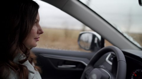 Brunette woman driver behind the steering wheel driving her crossover suv car