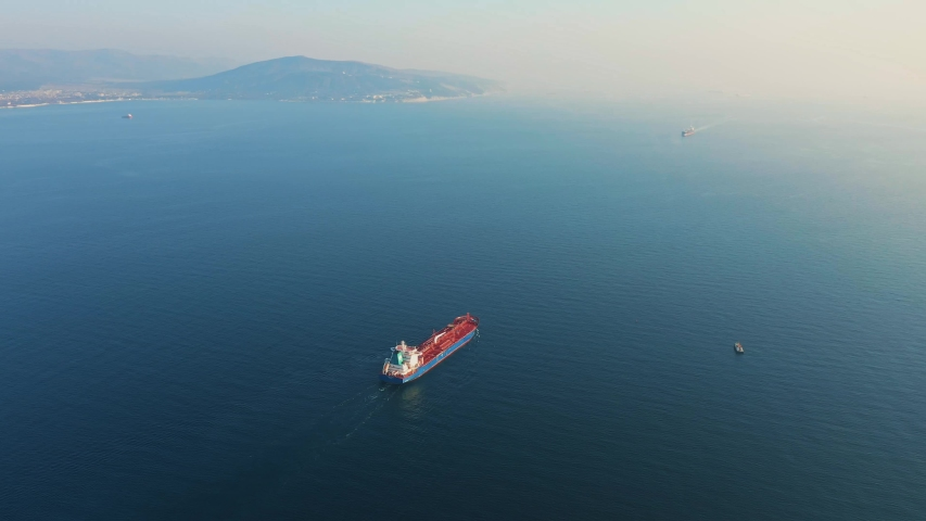 Aerial view, ultra large cargo or container ship at sea leaves port at sunset. Top down drone footage of tanker. Concept of transport logistics, maritime. | Shutterstock HD Video #1054098470
