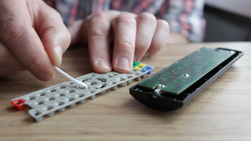 A man cleans the TV remote with an ear stick.  | Shutterstock HD Video #1054099793
