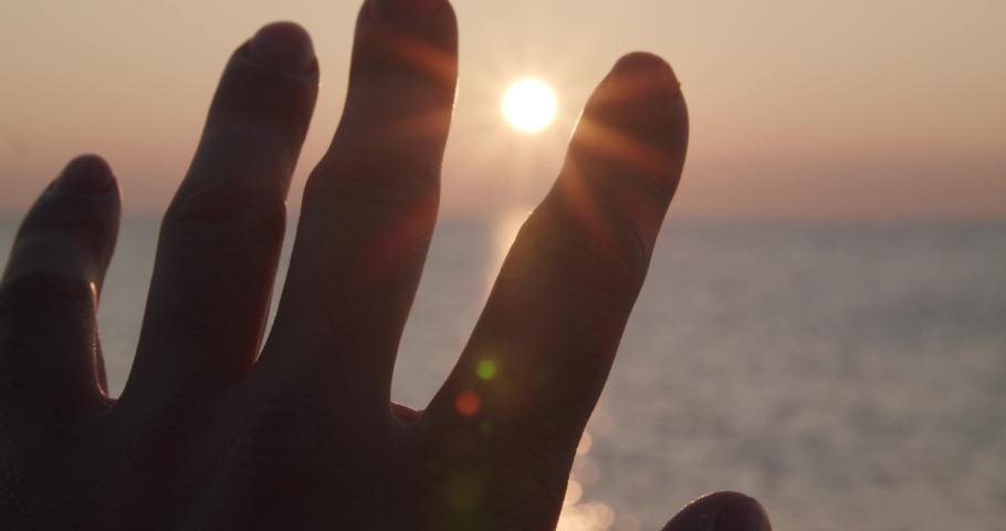 Close up focused foreground hand reaching sunrise, bokeh sea horizon, Almeria, Spain Royalty-Free Stock Footage #1054100429