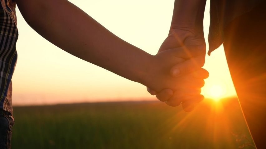 Happy family mom and son hold hands close-up teamwork. mother and boy kid together hands at sunset. parent girl and child happy childhood. lifestyle happy family mother day concept | Shutterstock HD Video #1054100669
