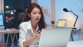 Young Asian business woman on video conference call, using laptop computer work late night. Remote meeting, work at home, internet technology, Covid-19 quarantine lockdown new normal lifestyle concept