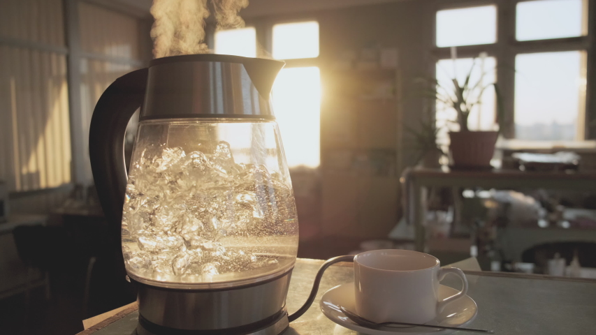 A transparent kettle of water boils against the background of the sunset shining through the window. The concept of coffee break and end of the working day. Royalty-Free Stock Footage #1054106030