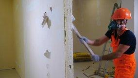 Worker in uniform and respirator destroys inner wall sledge hammer. Demolition work and rearrangement concept. Wall made of gypsum cardboard being destroyed. 4 k video
