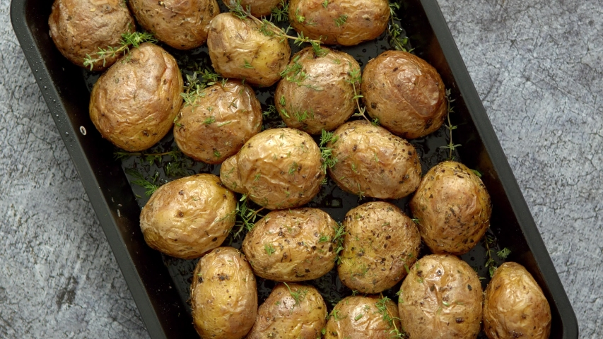 Oven baked whole potatoes with seasoning and herbs in metalic tray. Roasted potatoes in jackets. Top view. Close up. | Shutterstock HD Video #1054106462