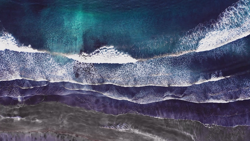 Aerial view of beautiful beach with view of ocean waves and water crashing on to sandy shore from top angle. Faroe Islands beach with waves crashing to shore. No people, epic dramatic wild beach