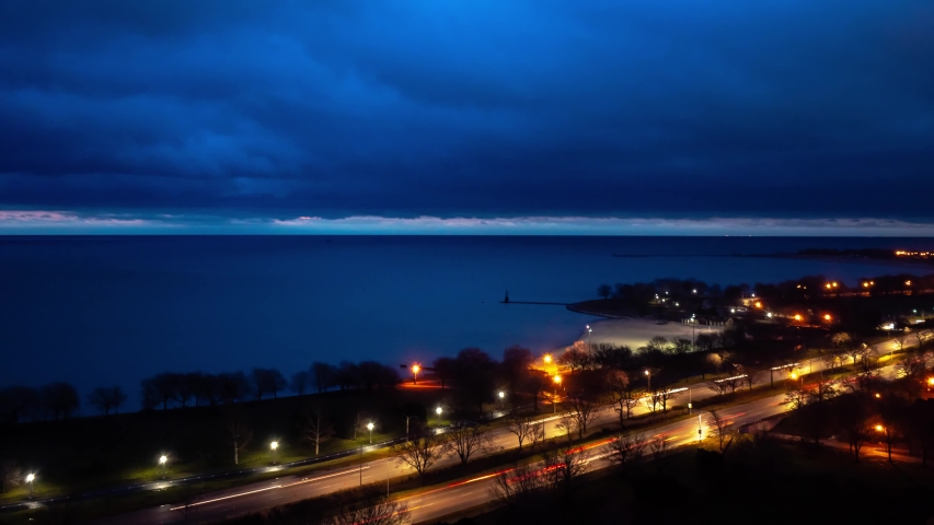 Beautiful aerial night time lapse of traffic and light trails on Lake Shore Drive in Chicago as heavy cloud cover moves over the calm water of Lake Michigan.