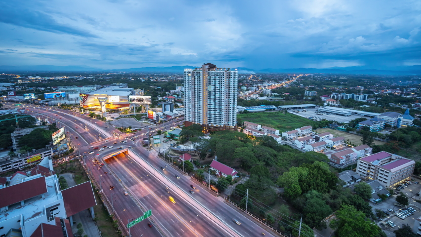Wide angle aerial view of traffic trails on a busy juncture in Chiang Mai, THAILAND - June 6,2020. Time lapse Aerial view Chiang Mai City | Shutterstock HD Video #1054110110