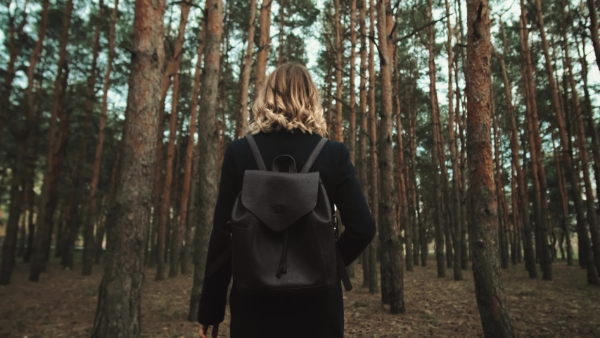 Young beautiful girl walks through a pine forest in a coat and with a backpack. Beautiful background. 4k Blonde. Rest alone. Self-isolation in nature, Young Student Girl Running through the Forest  | Shutterstock HD Video #1054110617