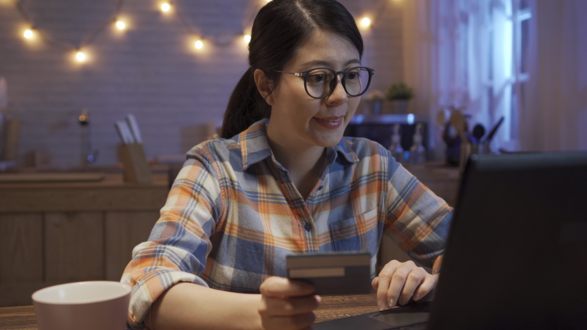 Asian japanese young woman in glasses holding credit card and typing keyboard laptop for shopping online payment. girl using debit card using internet paying on notebook pc in home kitchen at night.