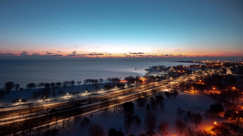 Beautiful vertically panning up aerial morning sunrise timelapse of the Chicago Lakefront along Lake Michigan with traffic passing by on Lake Shore Drive as the sun comes up over clouds on the horizon.