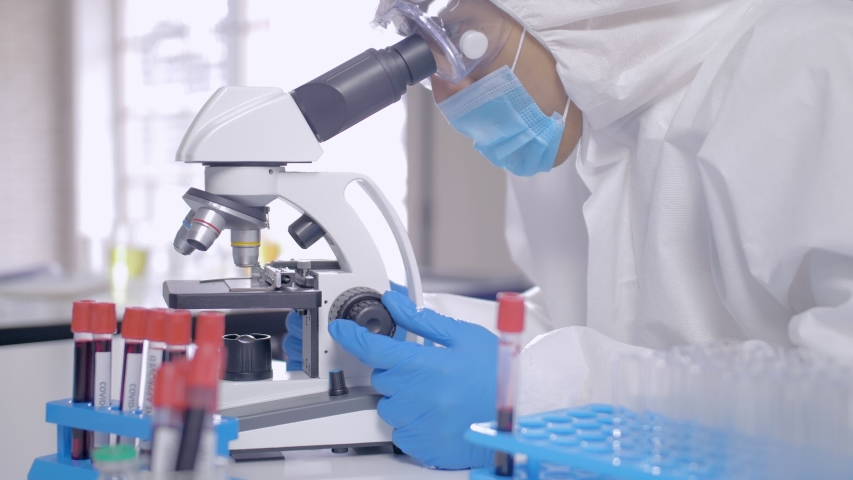 Scientist in PPE suite doing some research and looking through a microscope in laboratory	 | Shutterstock HD Video #1054115948