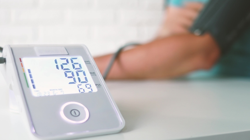 Man hand and white electric tonometer on table for measuring blood pressure Healthy concept. Measurement of pressure and pulse. Hypertension and hypotension | Shutterstock HD Video #1054117646