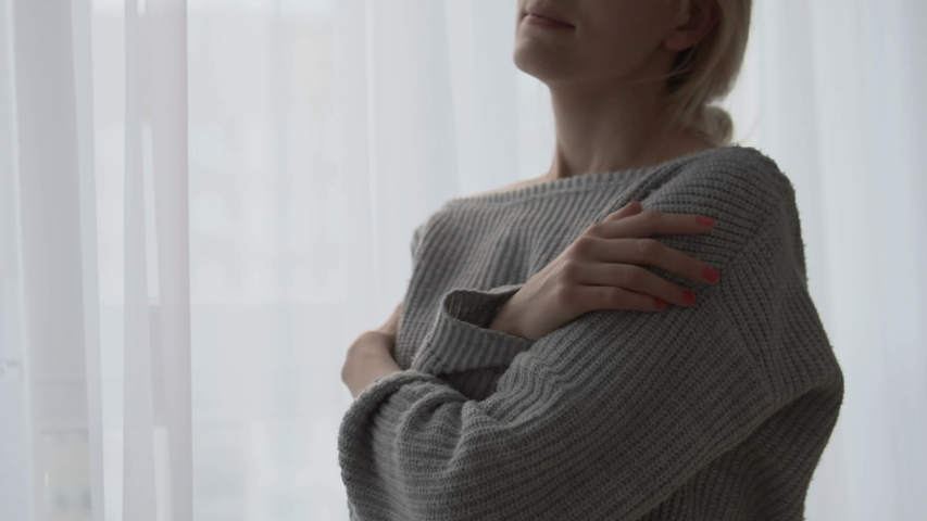 Unhappy lady in cozy knitted sweater standing by window, hugging herself, smiling