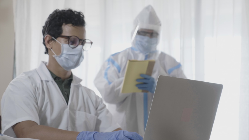Two men doctors or male healthcare workers wearing an apron and personal protective kit working on a laptop together in the hospital or clinic amid Coronavirus or COVID 19 epidemic or pandemic