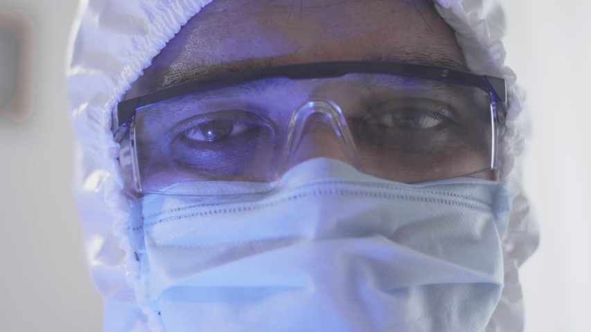 Close up shot of the tired and sleepy eyes of a male doctor or healthcare worker wearing personal protective kit while working in the hospital amid Coronavirus or COVID 19 epidemic or pandemic