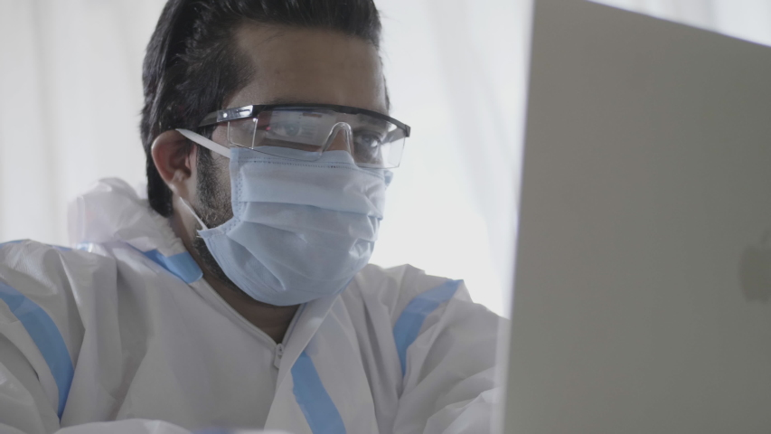 A male doctor or healthcare worker wearing personal protective kit is busy working on a laptop in the interior  hospital or clinic setup amid Coronavirus or COVID 19 epidemic or Pandemic