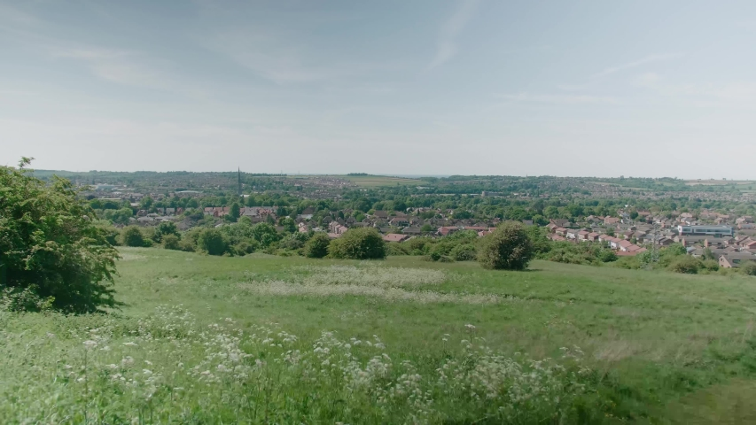 Grantham Town Lincolnshire UK East Midlands crop fields view in the distance of the town Summer day wind blowing grass and trees and crops high view point houses in view and st wulfram's church