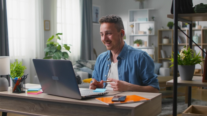 Young man talking on video calling in headphones at his laptop at home in the living room | Shutterstock HD Video #1054128245