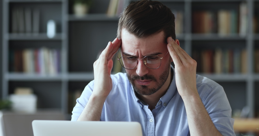 Stressed young man in glasses suffering from muscles tension, having painful head feelings due to computer overwork or sedentary working lifestyle. Tired employee overwhelmed with tasks in office.