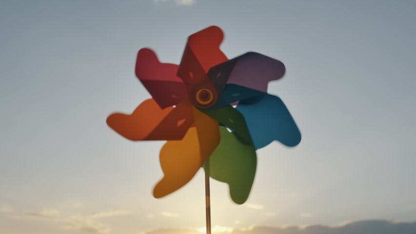Pinwheel rotating colored plastic with blowing wind against a blue sky, white clouds, silhouettes of city buildings on sunset slow motion. Symbol of freedom and life. Toy spinner. Bright disk of sun Royalty-Free Stock Footage #1054132631