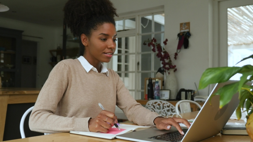 Young mixed race woman with afro working from home in front of laptop | Shutterstock HD Video #1054132751
