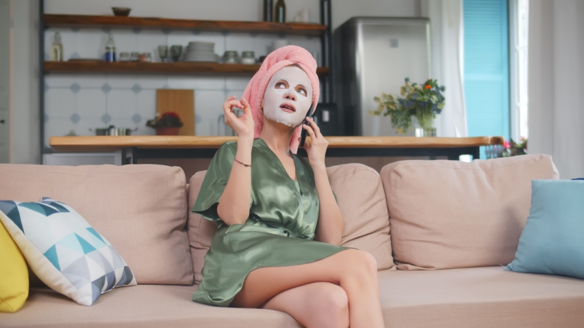 Young pretty woman in bathrobe with cotton facial mask talking on smartphone sitting on couch and enjoying home spa. Hygiene and skin care concept Royalty-Free Stock Footage #1054132889