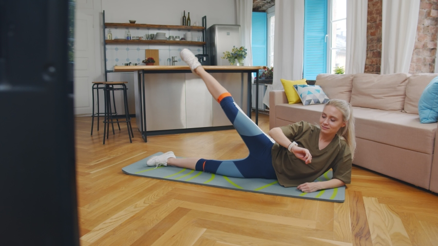 Attractive sporty woman working out at home, doing pilates exercise in front of television in her living room. Pretty young girl on mat doing aerobics exercises watching sport tv channel   Shutterstock HD Video #1054132904