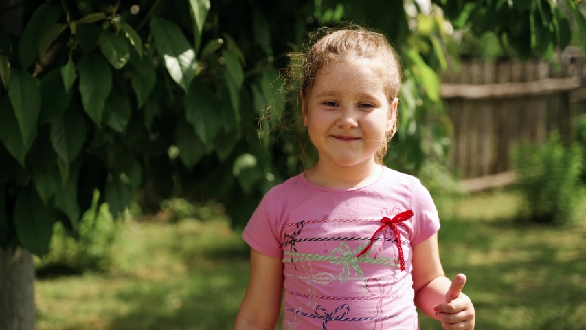 Little preschool girl show thumbsup. She is outdoors in summer. Green leaves behind her