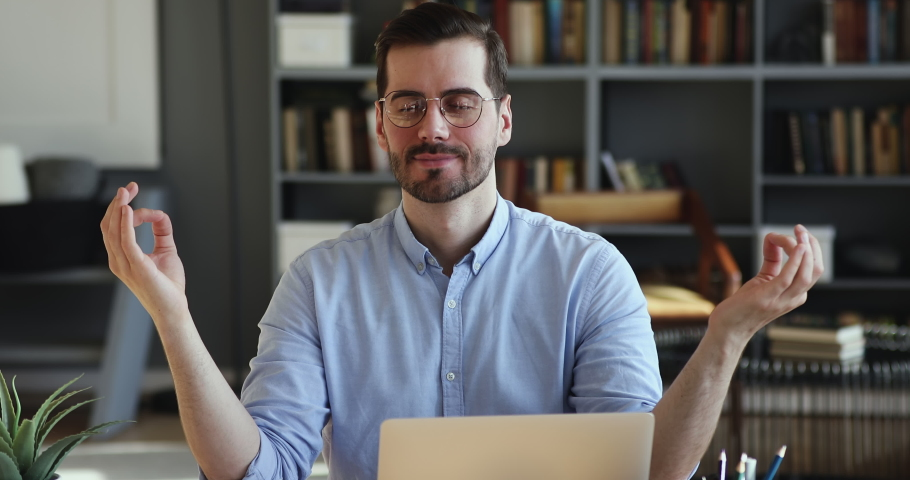 Peaceful relaxed young handsome male worker in eyewear sitting at workplace with folded in mudra gesture hands, reducing stress during workday, meditating or doing yoga breathing exercises in office. | Shutterstock HD Video #1054134032