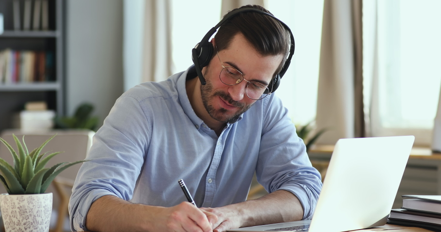 Focused young businessman in eyeglasses holding video conference call with clients, wearing wireless headphones with microphone. Skilled happy salesman advertising goods to customers, writing notes. Royalty-Free Stock Footage #1054134035