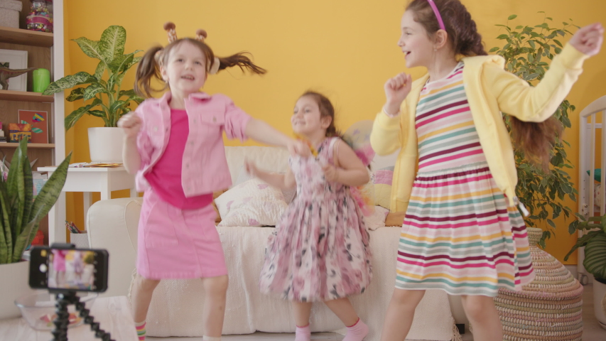 Shooting a Video Blog for Children with Smartphone. Production of Kid's Content. Three Cute Cheerful Little Caucasian Girl Dancing and Laughing, Cozy Interior with Yellow Wall on the Background. Royalty-Free Stock Footage #1054135160