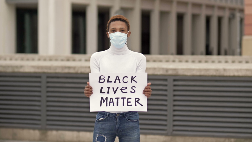 Poster BLACK LIVES MATTER in the hands of a black guy. Stop Racism concept. | Shutterstock HD Video #1054137965