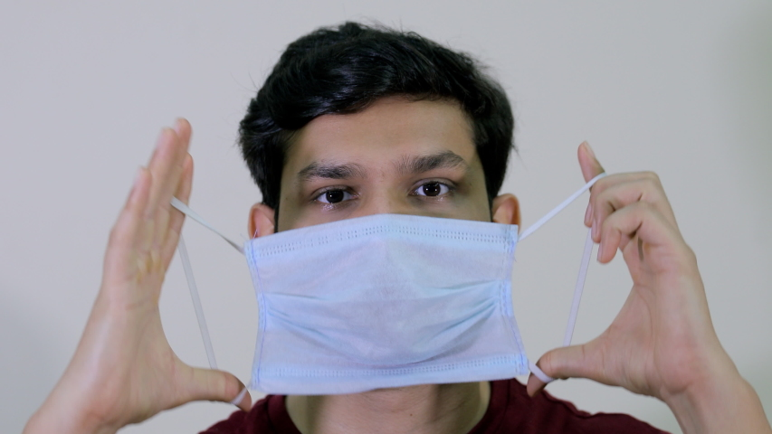 A young attractive boy removes his protective medical mask to breathe fresh air. Closeup of an Indian guy takes off his surgical mask during the Covid-19 pandemic against the white background Royalty-Free Stock Footage #1054138925