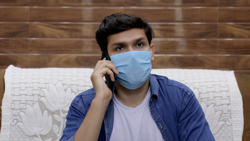 Attractive Indian guy talking on his smartphone while wearing a surgical mask. A young handsome boy talks to his friend over a phone call while sitting on a sofa during the coronavirus outbreak Royalty-Free Stock Footage #1054138946