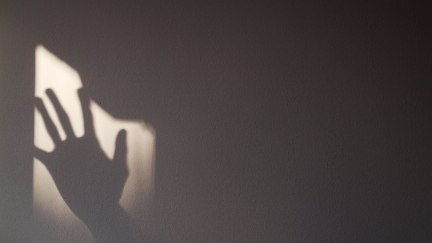 Shadows of hands on the wall. Games with light and shadow. Abstract shadows. Silhouettes of hands. Golden sunlight through the curtains. Fingers tap on glass. | Shutterstock HD Video #1054143281