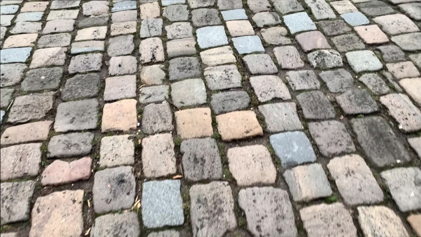 Ancient paving slabs of the ancient city, natural stone, paving stones moving under the feet of a walking person, the concept of a tourist walk, excursions to historical places | Shutterstock HD Video #1054143353