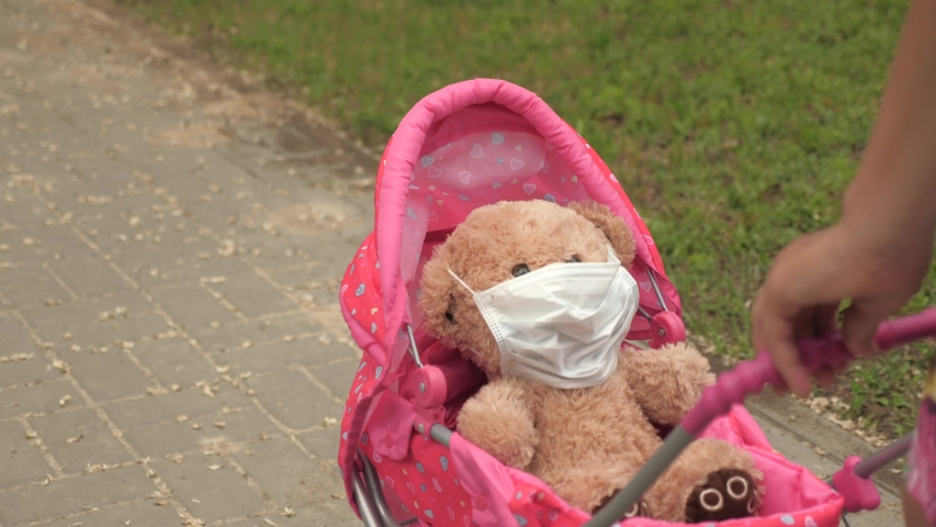 Child plays an epidemic and protects toy. girl on street with his favorite toy in protective mask. healthy childhood concept. little girl walks in park with a pram and a teddy bear in medical mask.