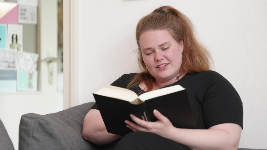 brunette plus size woman is first skeptical about what she is reading but then has a moment of aha