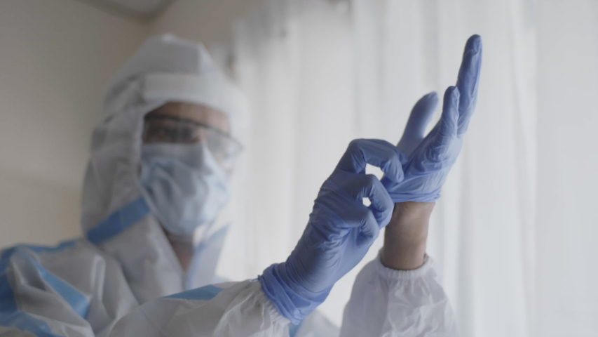 A close up shot of a doctor or healthcare worker in personal protective kit preparing and wearing hand gloves in the interior hospital or clinic setup amid Coronavirus or COVID 19 epidemic or pandemic